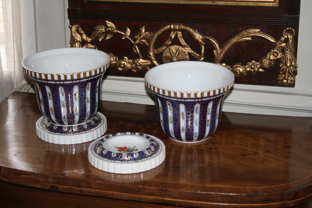 Blå, runde, kannellerede, dekorert med hvite striper med blomster, skåler under. Kopi av eldre utgave.