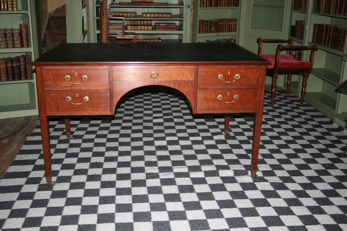 Skrivebord i mahogni, bordplate trukket med svart kunstlær. Fem skuffer på hver side av bordet. Beslag og trinser i messing.