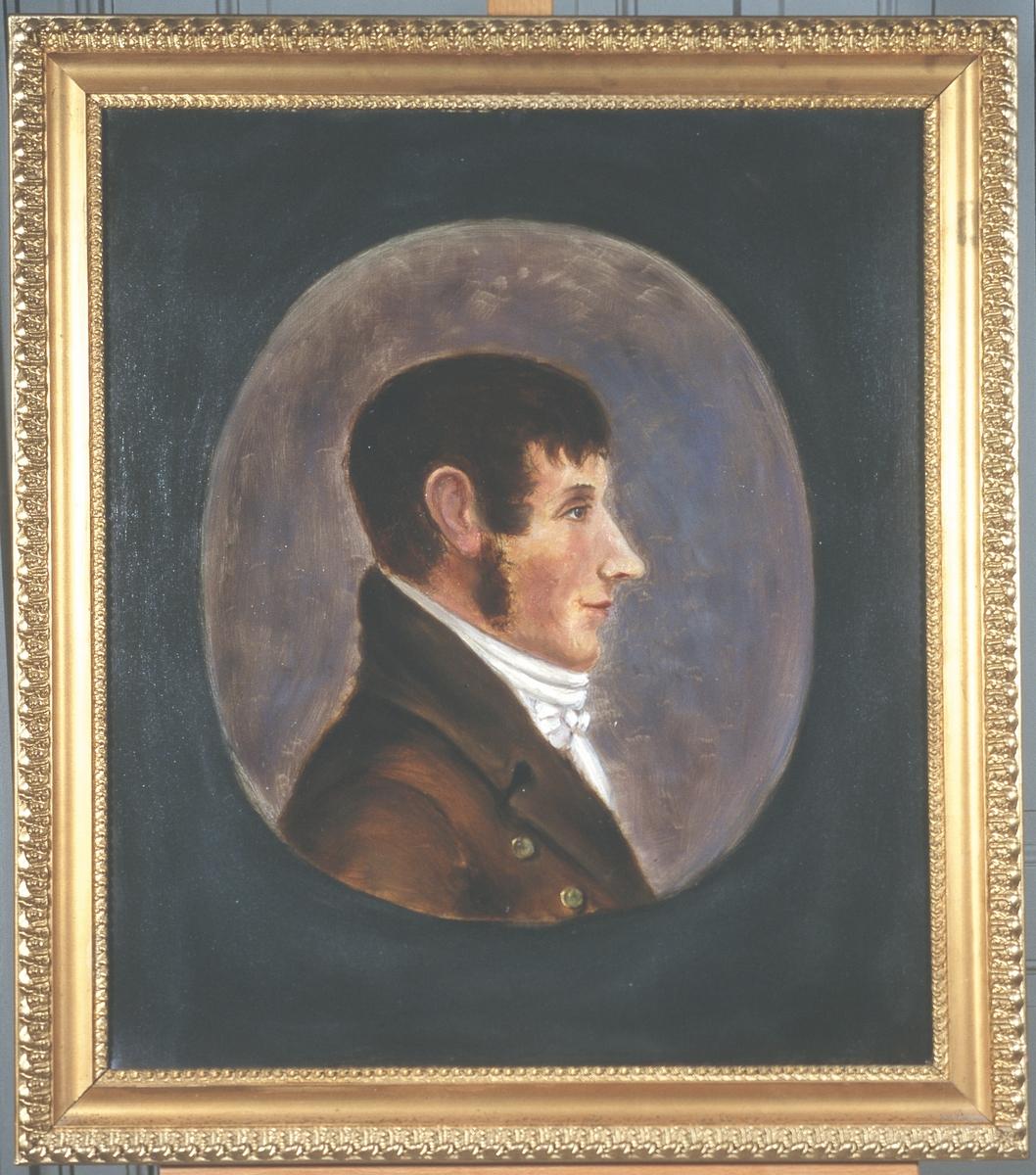 Portrett av Jørgen Aall.  Mann med brunt hår, framoverkjemmet, og brunt kinnskjegg.  Brun kledning og hvit skjorte/halsbind.  2 synlige knapper.  Innskrevet i oval, lysere enn resten av bakgrunnnen