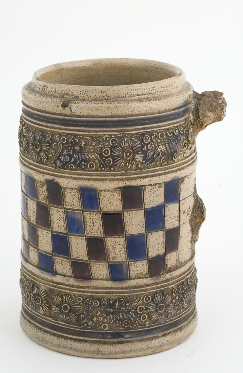 """Krus i grå keramikk av en type som stammer fra Westerwald-området i Tyskland. Karakteristisk er risset og semplet dekor og pålagte relieffer, farget med koboltblått og senere også manganfiolett, under klar saltglasur. Dette lave sylinderformede kruset kalles """"Humpen"""" og ble masseprodusert gjennom hele 1600- og 1700-tallet.   Lokk i metall mangler."""