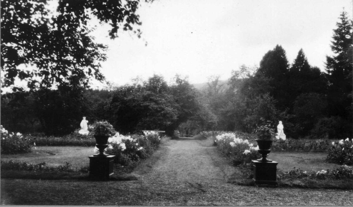 Partierrehaven på Eidsfoss hovedgård i Hof. Blomster og hageskulpturer.