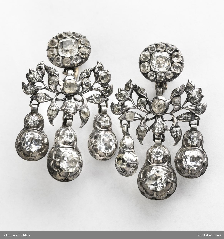 """Huvudliggaren: """"A-B: Örhängen. C: Etui. Örhängen. Av bergkristall med silverinfattning. I etui, märkt 'SSB[?]'."""""""