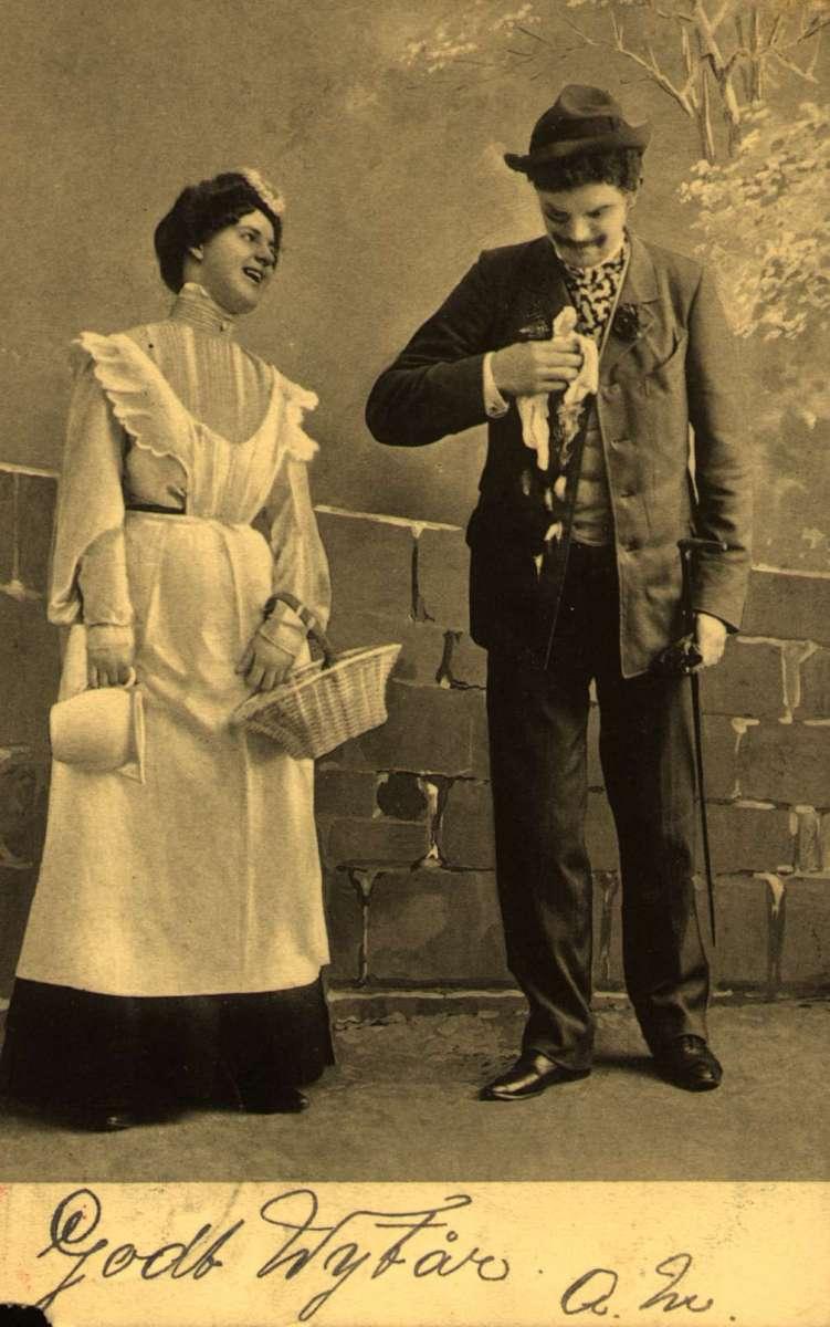 Postkort. Nyttårshilsen. En mann og en kvinne i munter samtale.  antakelig en scene fra en revy eller et teaterstykke. Stemplet 30.12.1904.