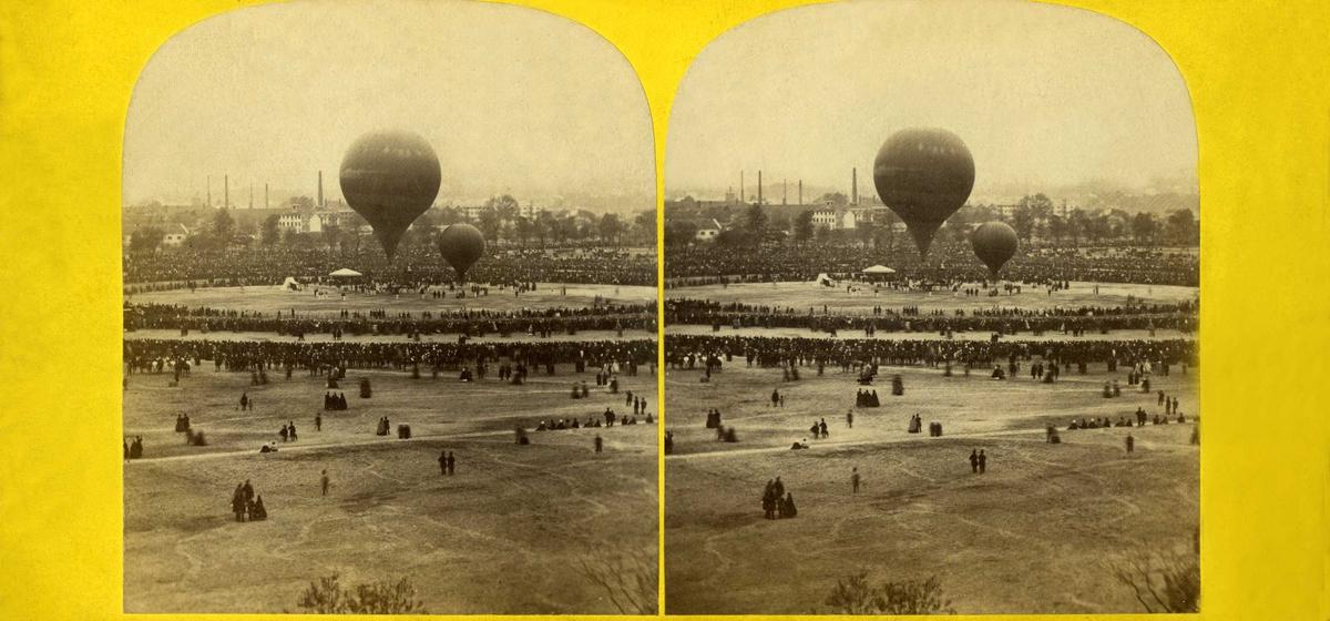Antatt Champ de Mars i Paris i oktober 1863. Stereoskopi. Åpen plass med mennesker og to luftballonger.