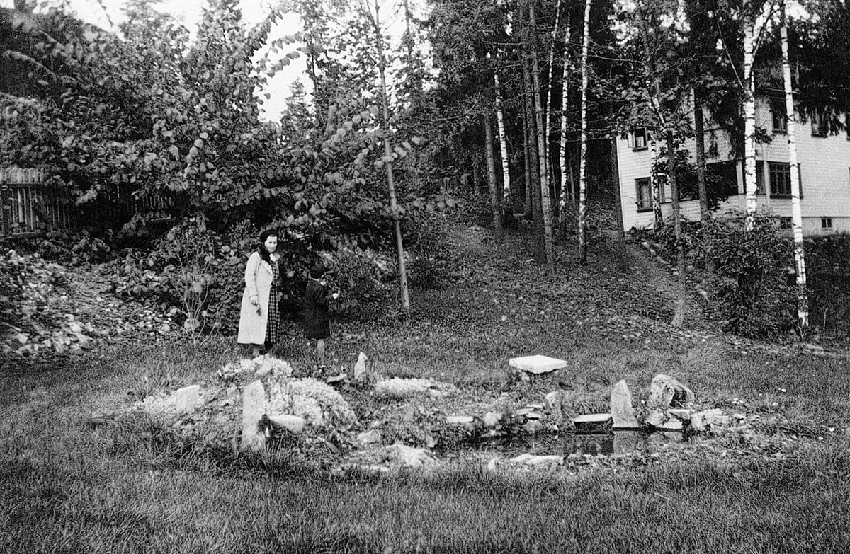 Hjørdis Fougli t.v. i hagen ved huset på Jar, Bærum, Akershus, sammen med sønnen Anders (født 1940). Like nedenfor på bildet kan man se dammen i hagen.