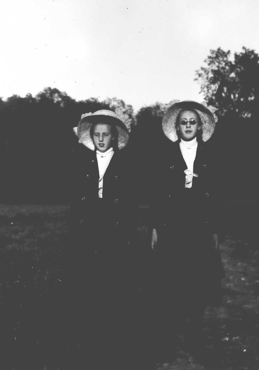 To søstre med lange skjørter og stråhatter.