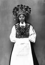 Studiofotografi av kvinne med brudedrakt og brudekrone. Ståe
