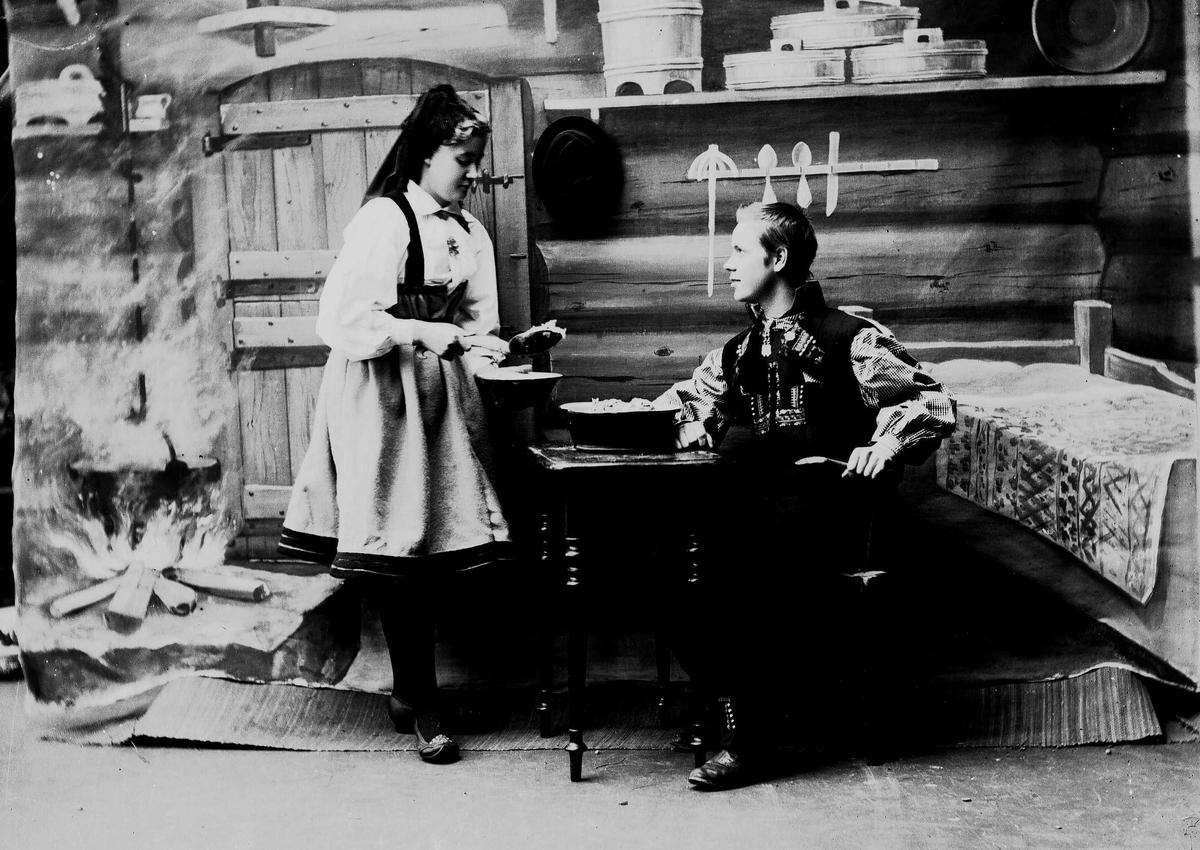 Studioportrett av mann og kvinne i nasjonaldrakter. Kvinne holder sleiv med mat i hånden og serverer mannen som sitter ved et bord. Bakgrunnen er malt og viser seterinteriør. Til venstre står kjelen på ildstedet og til høyre står seng og vegghylle med tiner.