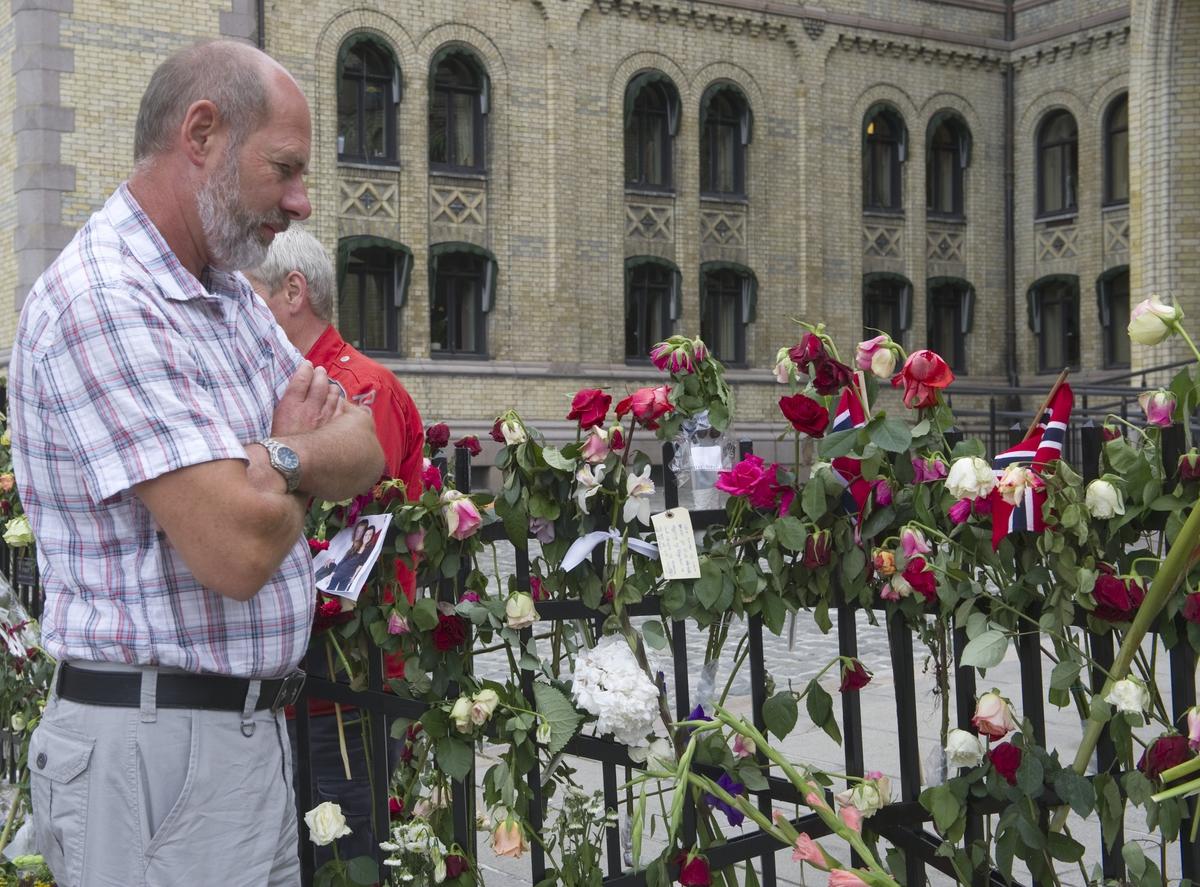 """""""Sorg i det offentlige rom"""". Folk ser på blomster og hilsener utenfor Stortinget."""
