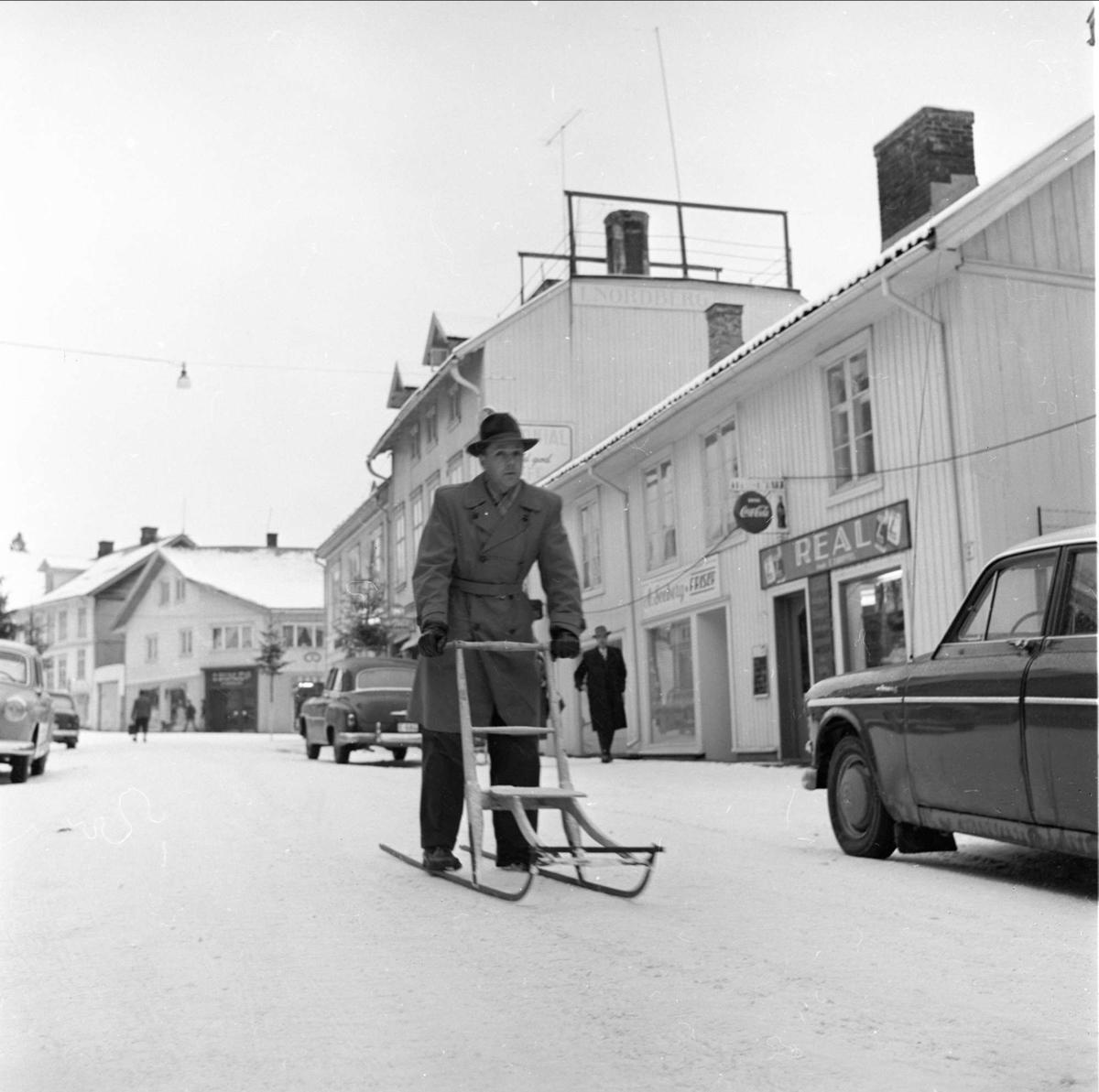 Gjøvik, gatebilde, mann med sparkstøtting på bytur, 03.01.1961