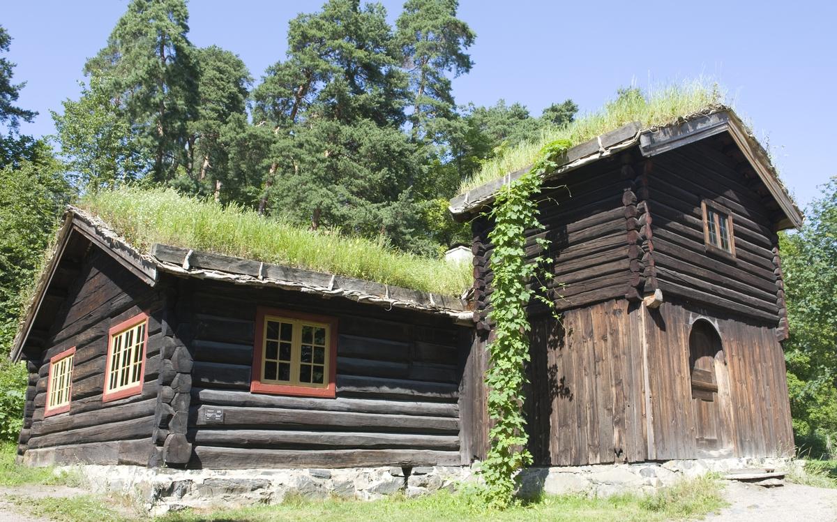 BARFRØSTUE FRA GAMMELSTU TRØNNES I STOR-ELVDAL, 1670  Overført til museet 1903, gjenoppført 1905   Huset har fått navn etter barfrøet, et toetasjers tilbygg som er plassert foran huset og danner inngangsparti. Denne konstruksjonen forekommer bare i Østerdalen og i tilgrensende trakter i Sverige. Barfrøet ble gjerne bygd på et eksisterende hus, som her, og var på moten å bygge i noen tiår rundt 1800. Det ble brukt til oppbevaring av klær, redskaper og utstyr.   På Gammelstu Trønnes har det stått hele tre barfrøstuer. Museets stue var sommerstue, en større og nyere var vinterstue, og den minste og eldste var drengestue.   Huset hadde opprinnelig en eldre type planløsning, med tre rom – forstue, kove og stuerom – men det har blitt ombygd flere ganger. Inngangsdøra har blitt flyttet, og nå kommer man rett inn i stuerommet via barfrøet. En vegg har blitt tatt ned, slik at huset nå består av bare to rom – stuerommet og et langt, smalt kammers. Sengene står i kammerset. Det er også et loft over kammerset, der det er flere soveplasser. Stuerommet har panelte vegger og himling, og store møbler og benker er plassert langs veggene. Rommet har peis, og en etasjeovn av jern. Rett til høyre innenfor døra står et stort melkeskap. Veggpanelet, inventaret og jernovnen er trolig fra 1808. Over høysetevinduet står innskriften: «Halvor Tollevsen Ingebor Nielsdatter Trønnes». Tvers overfor er stuas andre høysete, og her står det: «Denne Stue blev opbygget aar 1670 og Malet aar 1808»  (Tekst hentet fra By og bygd 43, 2010)