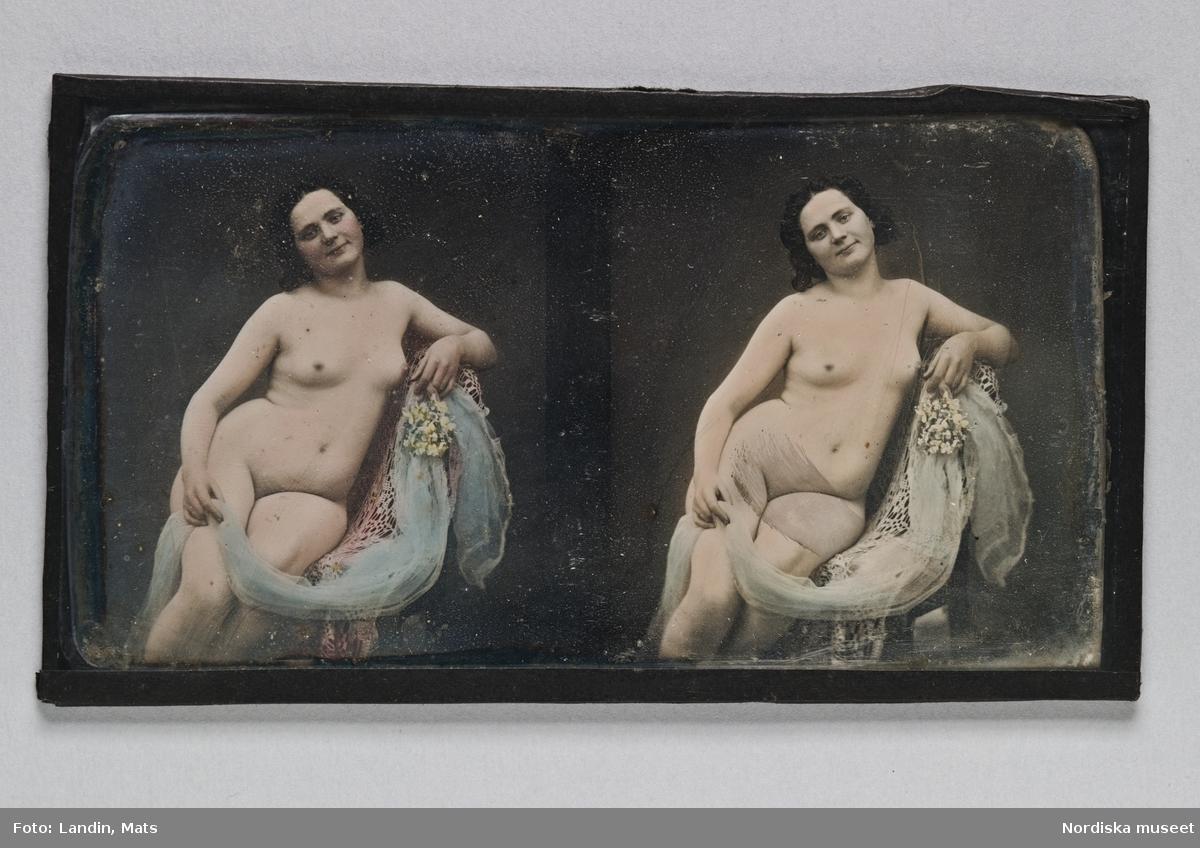 """Dagerrotyp / daguerreotyp, handkolorerad stereoskopbild. Föreställer knäbild av sittande, naken, mörkhårig kvinna. Håller en blå slöja och en liten bukett gula blommor i handen. Påklistrad svart kantlist av papp. Med blyerts på baksidan: """"Bergström Sthlm"""". Nordiska museet inv.nr 205467 - Sitting nude. Ninth-plate tinted stereo daguerreotype."""