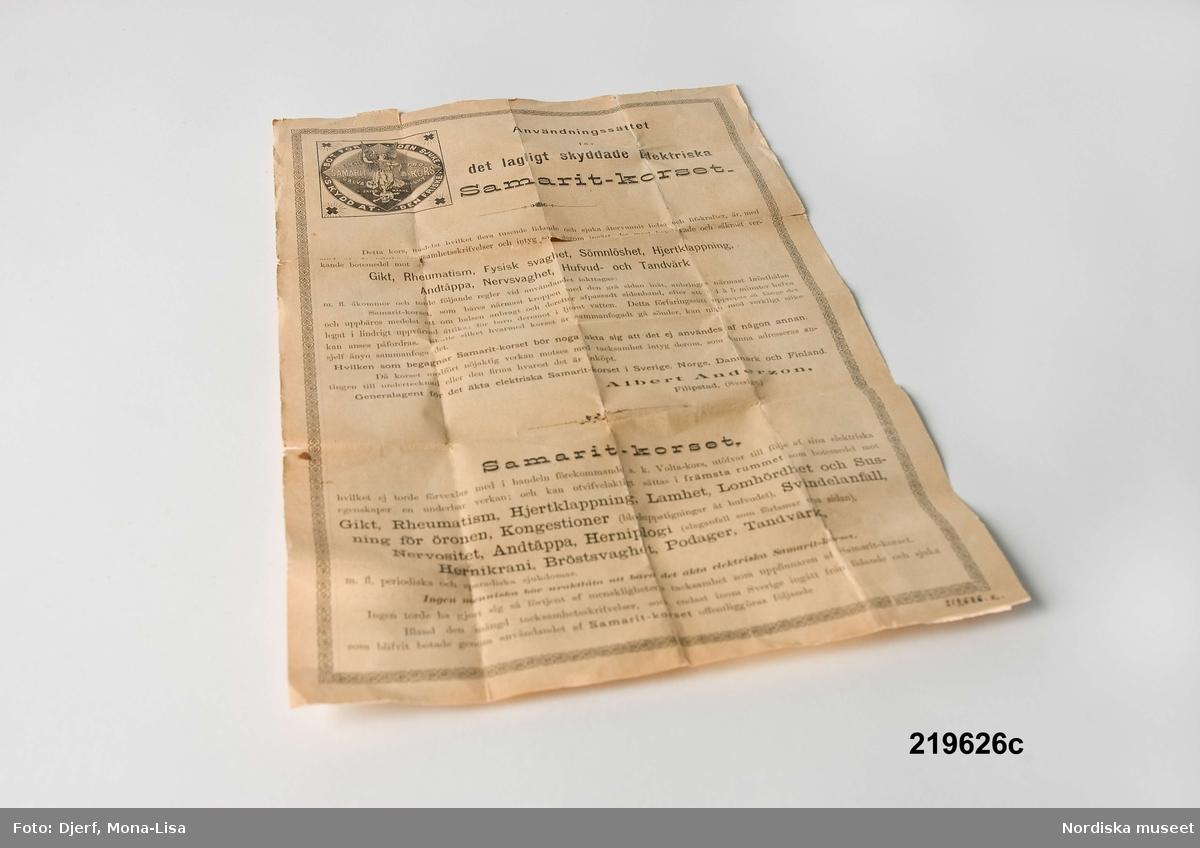 """Huvudliggaren: """"'Samaritkors', latinskt kors, en platta koppar, en platta zink med något emellan, i svart band; b) skyddskartong med svensk och engelsk text och 'fabriksmärke', c) tryckt reklam från Albert Andersson Filipstad, Generalagent; 'Jönköping 1891. Aug. Rickards Boktr.' G [odaterad] hittad i ett skåp i manbyggnaden från Edsängs by No. 3, Hälsingland; nu på Skansen."""""""