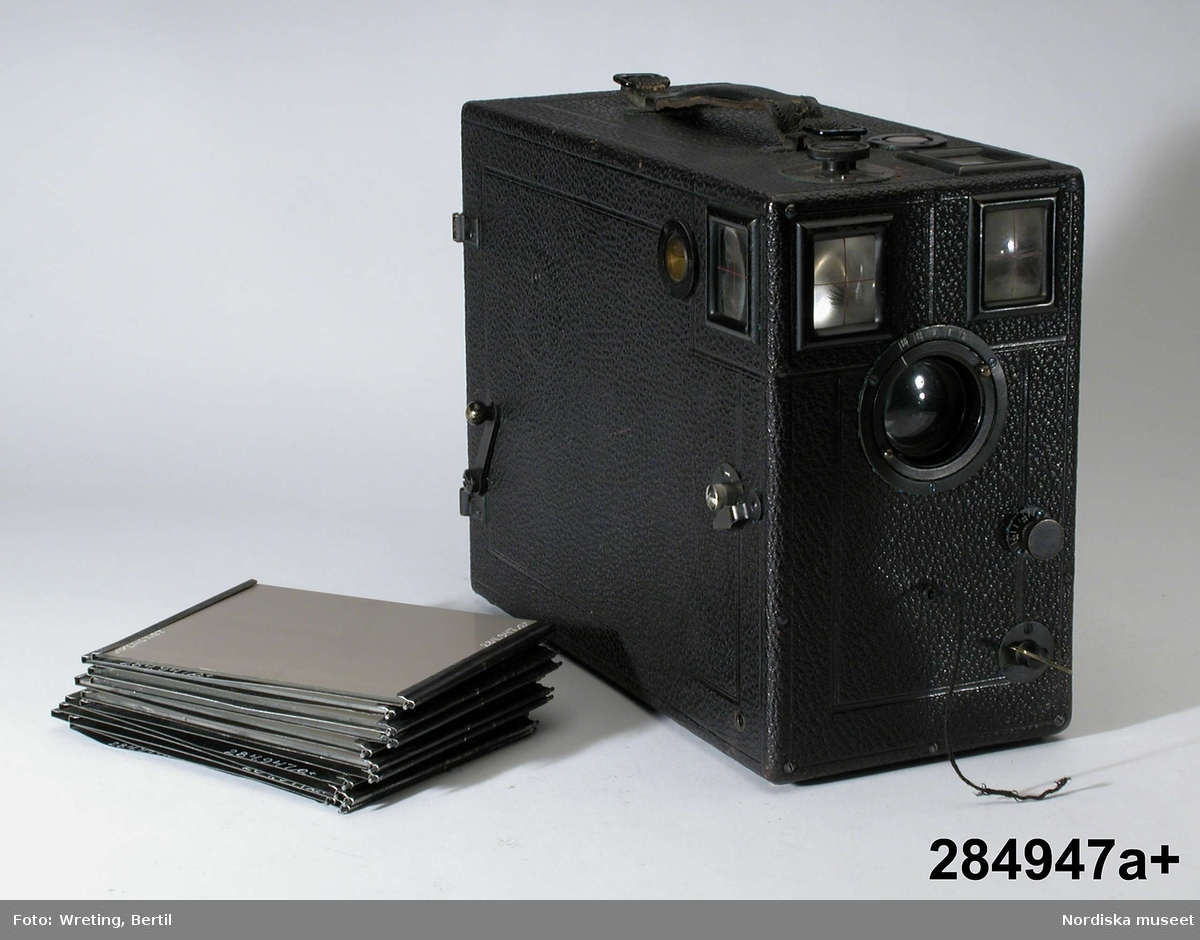 """Huvudliggaren: """"Kamera, lådkamera, magasinskamera; av trä överklädd med svart läder; vattenpass på två sidor;  (tillägg med blyerts; 12 st hållare för plåtar därav 6 en (?) glasplåt.) b) väska av brunt tyg."""