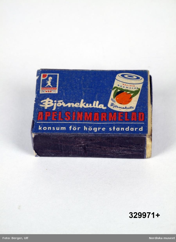 """Tändsticksask av papp och trä, plån på långsidorna, med instickslåda. Blå, Etikett med reklamtryck på ovansidan i form av en marmelad burk och text """"Björnekulla APELSINMARMELAD / konsum för högre standard"""". I övre vänstra hörnet en bild på en tändsticksask med """"Solstickepojken"""".  Asken är tom.  Tändsticksasken är tillverkad av Svenska Tändssticks AB omkring 1950-talet på beställning av Konsum/Björnekulla fruktindustrier.  Under 1900-talet användes ofta reklam på  tändsticksaskar/tändsticksplån i marknadsföringen av olika varor och tjänster. Askarna/plånen delades ofta ut gratis och många restauranger lät dem ligga framme på borden för gästerna. Under slutet av 1900-talet blir detta mindre populärt, delvis för att tändaren blir vanligare, men framför allt beroende på att färre rökte och att rökning inte längre förknippades med något positivt.  Tändsticksasken ingick i en större samling som ihopsamlats av givarna under sina bilresor under 1950-talet och fram till 1980-talet inom och utom Sverige. Ett urval ur samlingen gjordes av Nordiska museet 2009. /Leif Wallin 2009-09-24"""