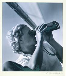 Kvinna med kikare. Ung kvinna med kort, blond, lockig frisyr