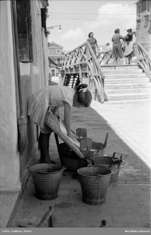 Flicka står på gatan och tvättar. Italien