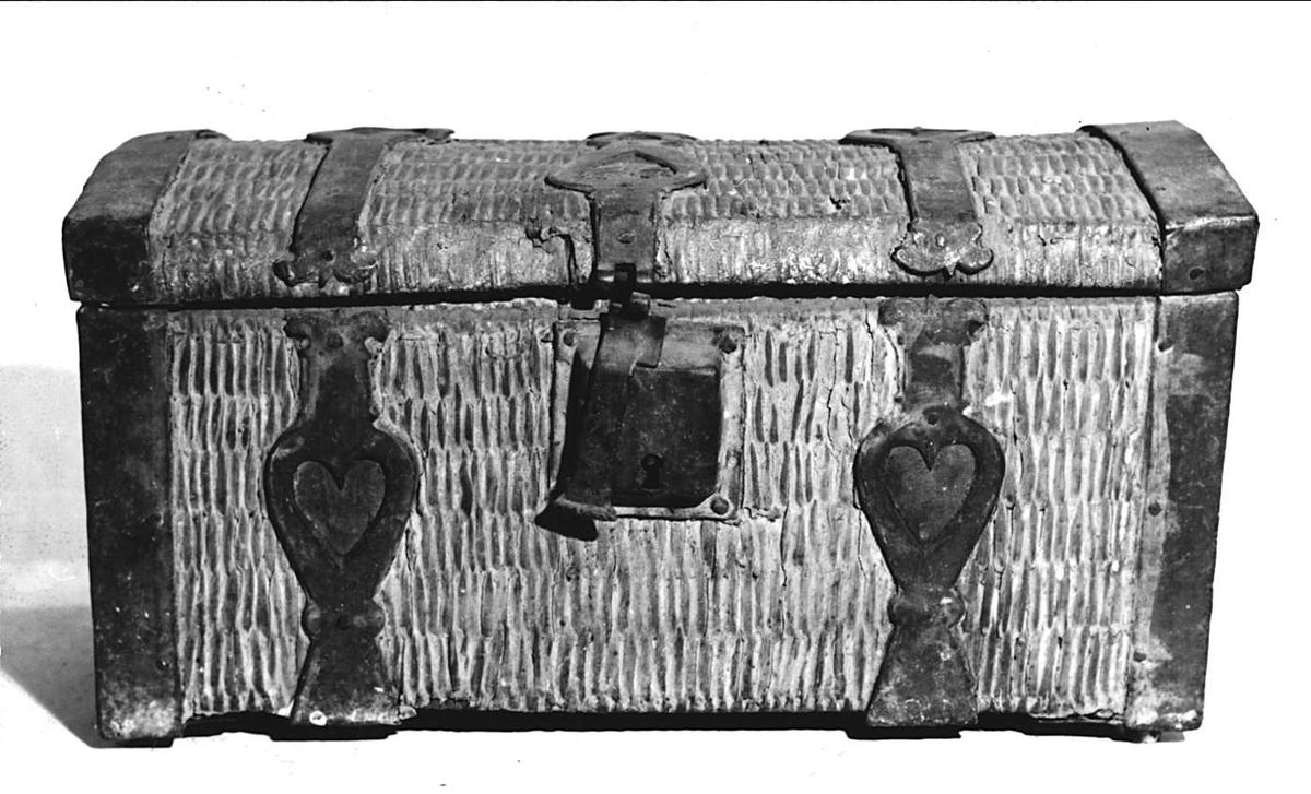 Liten kista flätad av vidjor tätad med något slags gulvit puts, järnbeslag, släta och profilerade med genombrutna hjärtan med läderfyllning. Invändigt klädd med linnelärft. Välvt lock. Bärringar.