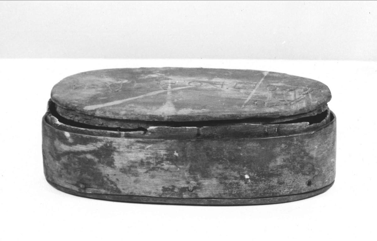 Ask av trä. Svept, oval med lock.Rester av rödbrun färg. Sydd med vidja. På locket inristat AAS ANO 1740 (fyran bakvänd) d 7 IUN -.