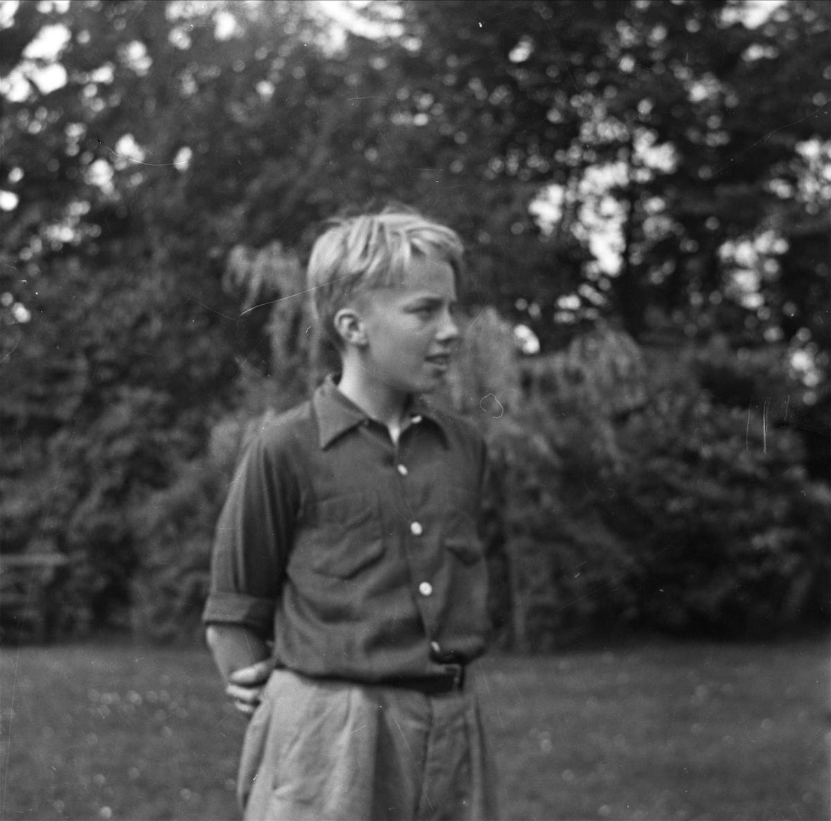 En pojke ute i trädgården