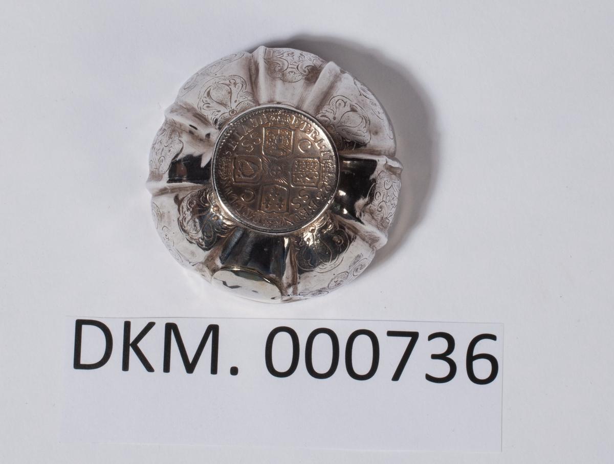 Liten sølvbolle dekorert med siselering. Bollen har myntmotiv i bunnen.
