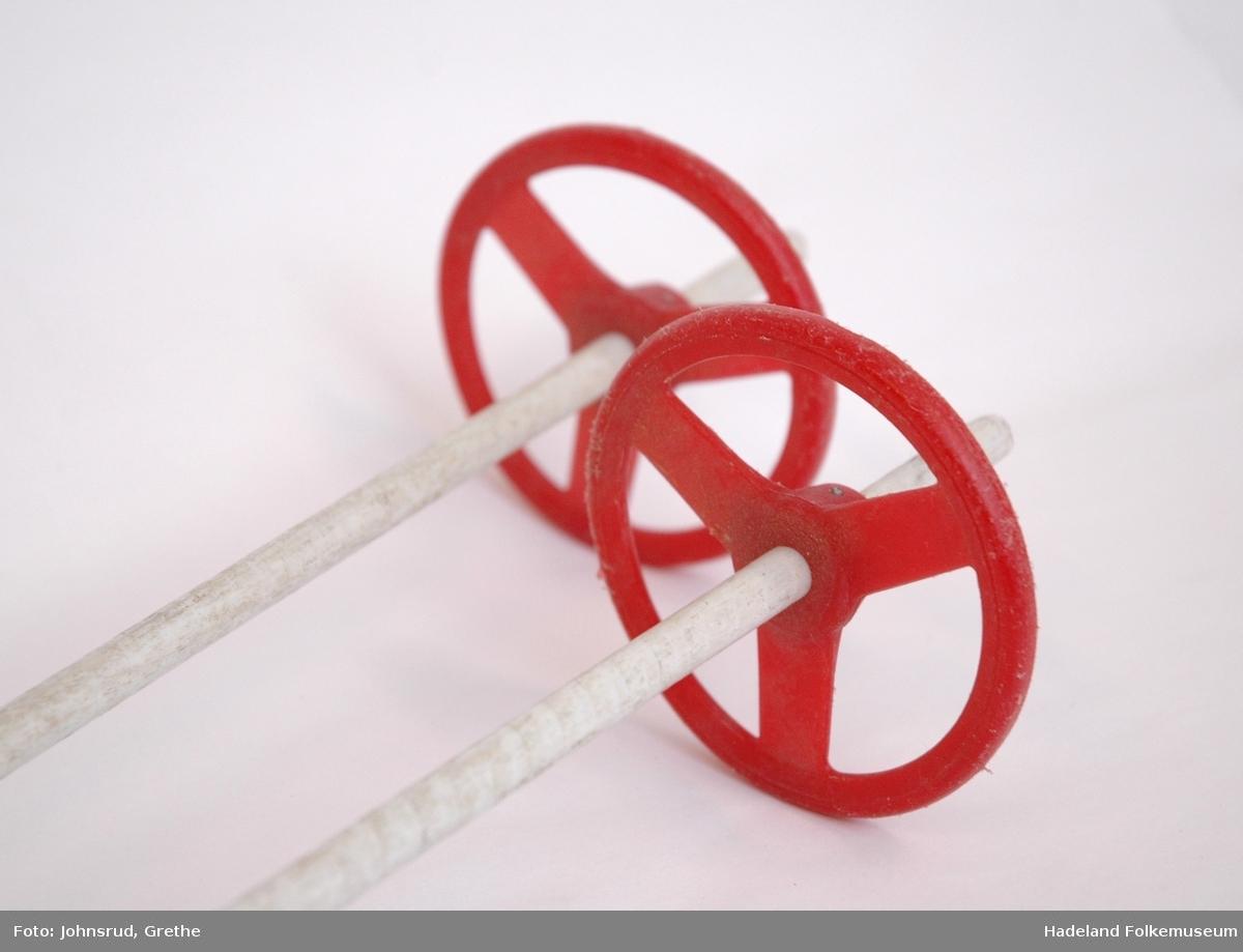 Hvite stenger med rødt håndtak og trinse i plast. Lærreimer til å ha rundt hånden.