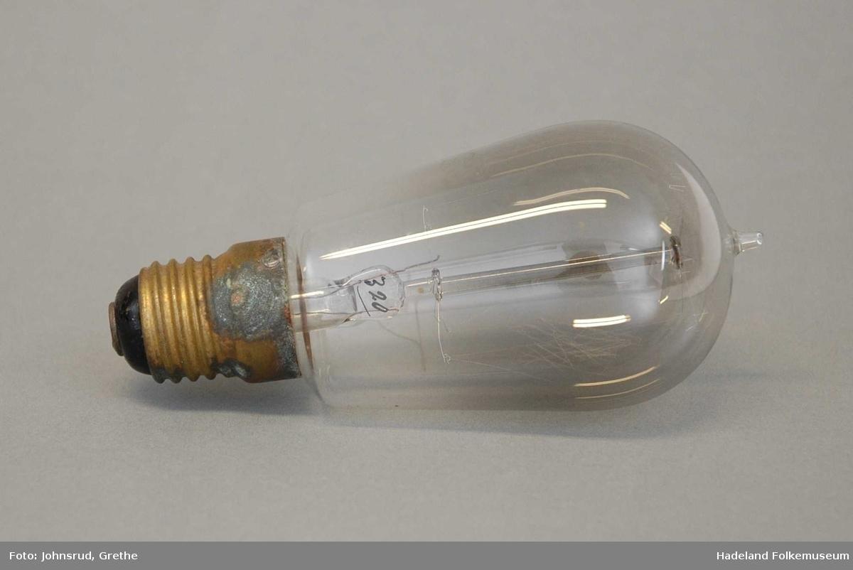 Til elektrisk belysning. Messingsokkel med gjenger. Glasset i kolben gjennomsiktig. Tupp i enden