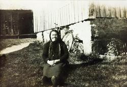 Gammel kone får ei kvild ved husveggen. Sveindal Grindheim senere Audnedal.