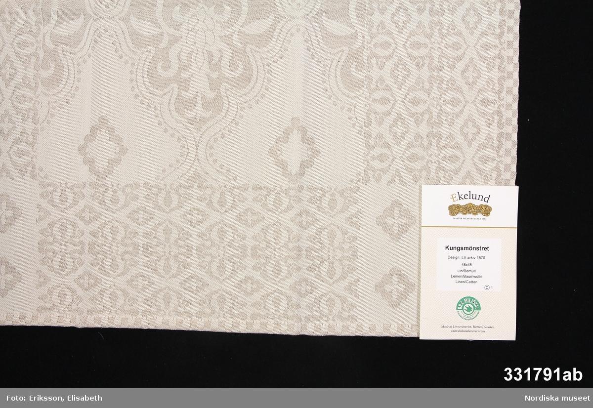 """Etikett av papp med tryckt text,, vikt på mitten, bildande 4 sidor. På framsidan text: """"Ekelund MASTER WEAVERS SINCE 1692 /  Kungsmönstret Design LV arkiv 1870. Lin/Bomull  Leinin/ Baumwolle  Linen/Cotton  I grönt Naturskyddsföreningens märkning: """"BRA MILJÖVAL Uppfyller miljökriterier  fastställda av Naturskyddsföreningen"""" med bild av konturerna av en svala i grönt. På följande """"sidor"""" text om tvät, behandling av linne, producentansvar (även på engelska och tyska), samt på baksidan information om Naturskyddsföreningens miljömärkning med rubrik """"Bra Miljöval är Naturskyddsföreningens miljömärke sedan 1990"""". Nertill """"Licensnummer 4-2000-0011-9 / Vävd av Morgan, Batchnr 51004, Kontrollerad av Lotta."""" Leif Wallin 2013-09-04"""