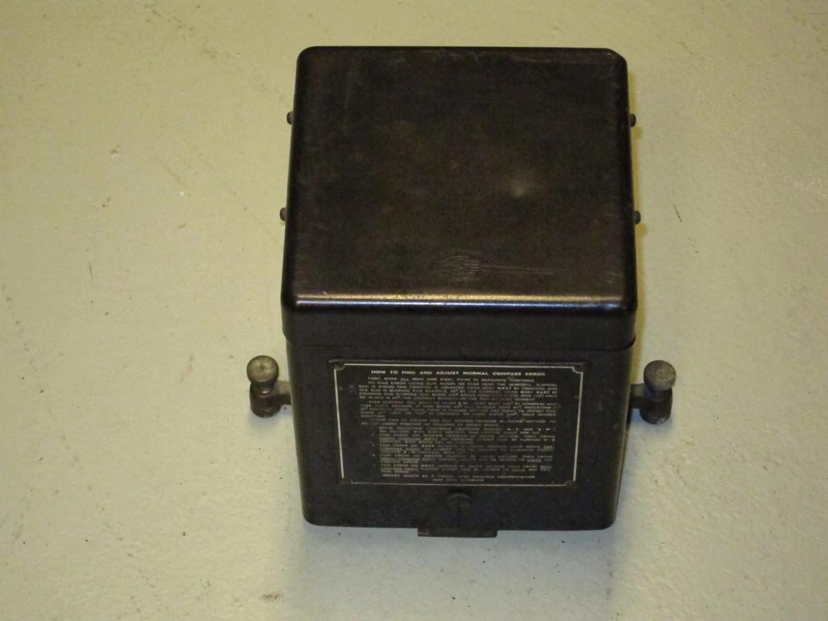 Sort boks med instruksjonsskilt på en side.(Måleinstrument for å finne kompassfeil.)
