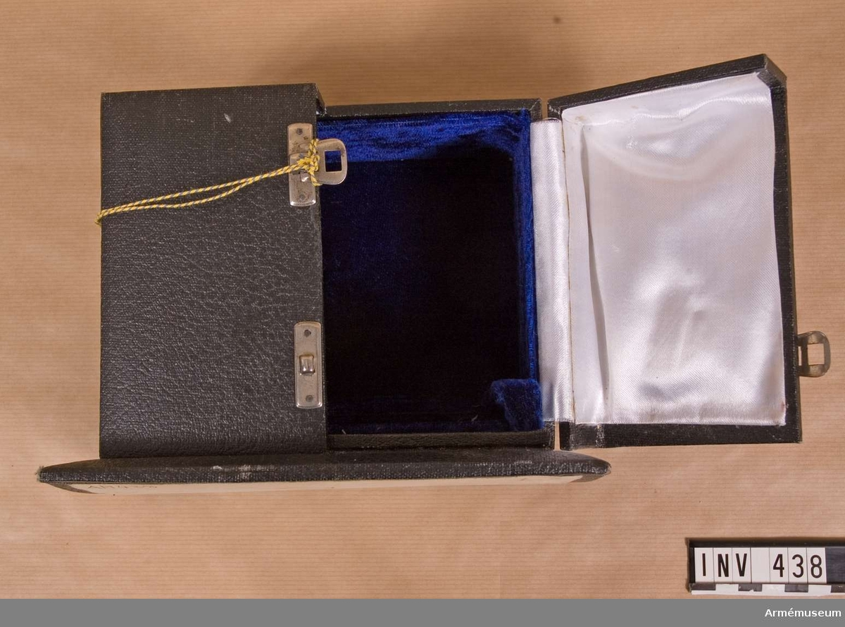 Fodral t minnestecken från 50. fallskärmsbrigaden, Agra. I svart klot. Mått, bottenplatta: 200x120 mm, ask: 170x140 mm. På bottenplattan står ett litet skåp med uppfällbara dörrar, vilka är försedda med två st. spännen. Dörrarna är invändigt klädda med vitt konstsiden. Skåpet är inrett med mörkt blålila konstfibersammet.