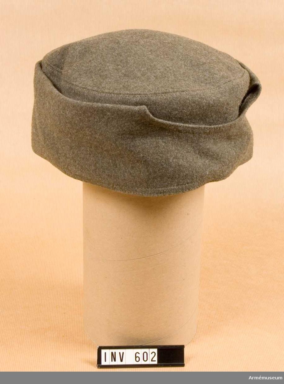 """Stl 57 och 58. Av kommiss. Rundmössa utan skärm med nedfällbart  yttre öron-, nack- och ansiktsskydd. Runt hål för ögon och näsa. Skyddet viks två gånger då det inte används. Fodrad med vadderat  bomullsfoder med märkning i kullen: """"I 13 1941."""" """"62"""" och """"för  57 o. 58""""."""