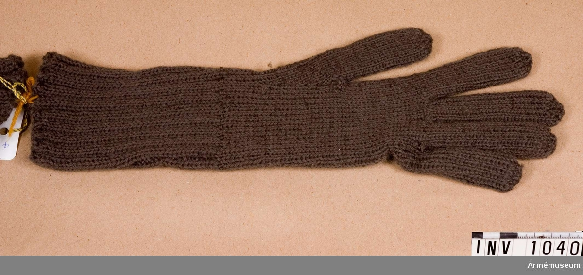 Samhörande nr är 1017-1059, 1062-1063, 1072-1073.Vante t uniform 1942 kv, ylle.Gråbrungrön, stickad med fem fingrar, en rät maska - en avig. Mudden vid handleden är 120 mm hög, stickad i två räta - två aviga maskor. Bäres till uniform kv m/1942. Har tillhört mobilibseringsutrustning vid Armémuseum.