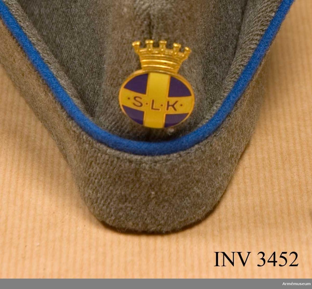 Gott skick. Diameter: 20 mm. Höjd med krona: 25 mm.Lottabroschen fästes i mössan ovanför den uppvikta kanten. Utförd av Sporrongs i förgylld metall och med framsidan täckt med i emalj, ett gult kors på blå botten. På det horisontellt liggande gula fältet står i blå emalj kantat med guld: S L K (Riksförbundet Sveriges Lottakårer). Märket är krönt med kunglig krona. Sitter på mössa AM.003453.