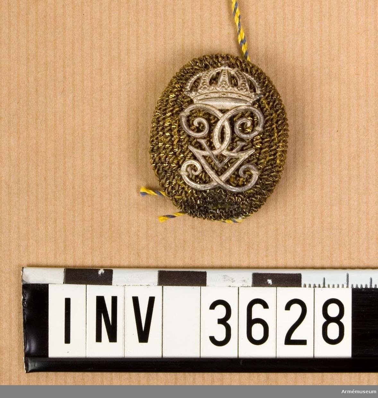 Pompong m/1865 med G V:s namnchiffer m/190B, Infanteriet. Oval  form med på den välvda framsidan guldsnodd lagd tätt, täckande  hela ytan. Därpå fäst Gustaf V:s namnchiffer i silver, ett G i  spegelmonogram krönt med kunglig krona. Ett på längden gående  hål för genomstickning av plym m/1865, 1975:3627. Till mössa m/1865, parad.