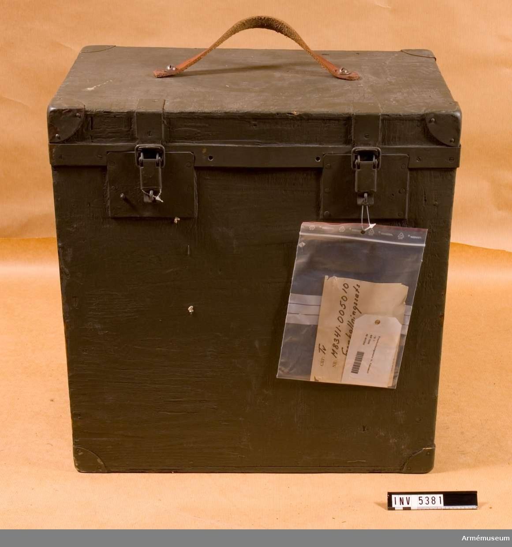 Framkallningssats M 8341-0050#10.Framkallningsapparat för film, bestående av spolapparat med två spolar och tre st behållare, doppvärmare, grön trälåda, plåt för okänt ändamål 80 x 170 mm.Spolapparaten är avsedd för film eller papper med bredden c:a 330 mm och består av en ram som håller spolarna. Anordningen sänkes ned i en uppifrån oval behållare. Tre behållare finns,  de förvaras instuckna i varandra. Höjd c:a 360 mm, längd 400  mm, bredd 200 mm.Doppvärmaren är försedd med gummikabel och jordad stickpropp. Märkt: Backer Elektro-värme AB SÖSDALA WATT 250 W  TYP (blankt fält)  VOLT 220 V  N:R 409 .