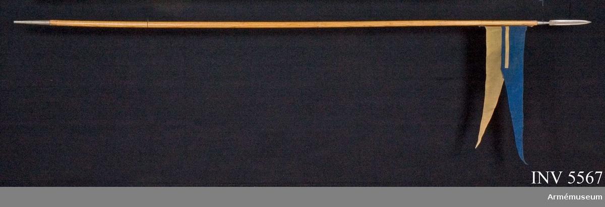 """I en av skenorna finns tre öglor vari lansflaggan fästes. Tvåeggad klinga och doppsko tillverkad av Eskilstuna Jernmanufakturaktiebolaget. Spets/doppsko märkt """"GL PIF""""."""