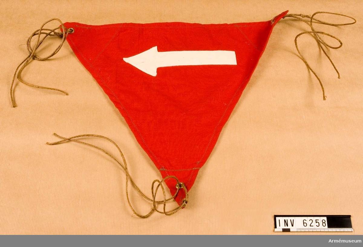 Röd stationsskylt av tyg med vit pil. I hörnen öljetterade hål för snören. Mått 400 x 400 x 400 mm.   I par: AM.6257-6258