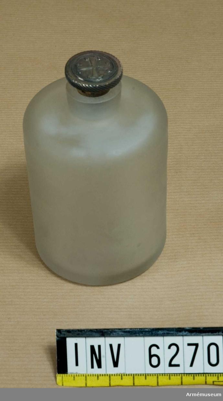 Av matt glas, försedd med en 10 mm hög hals med propp. Proppen är  av kork med silverbeslag, räfflad kant ooh ett kors, snarlikt ett ankarkors.