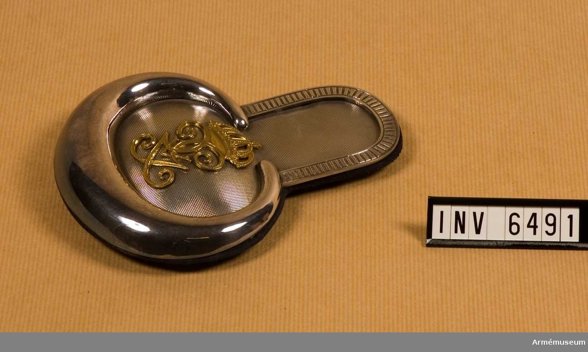 """Av massivt silver fodrad m mörkblått kläde. På mattan av silver (rutmönstrad) Gustav V:s spegelmonogram m/1908 i förgyllt silver, 60 mm högt. Haken märkt """"Milit.Ekip.Akt.Bolag""""."""