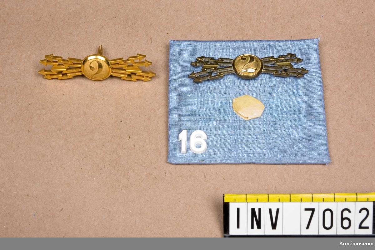 På platta två stycken kompani- och avdelningsmärken m/1902, Fälttelegrafkåren. Plattans storlek 80 x 70 mm.
