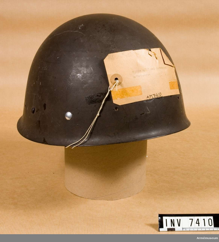 Gråmålad stålhjälm med inredning i form av en skumgummiring (som börjat torka) samt svett- respektive hakrem i läder. Ställbar storlek.