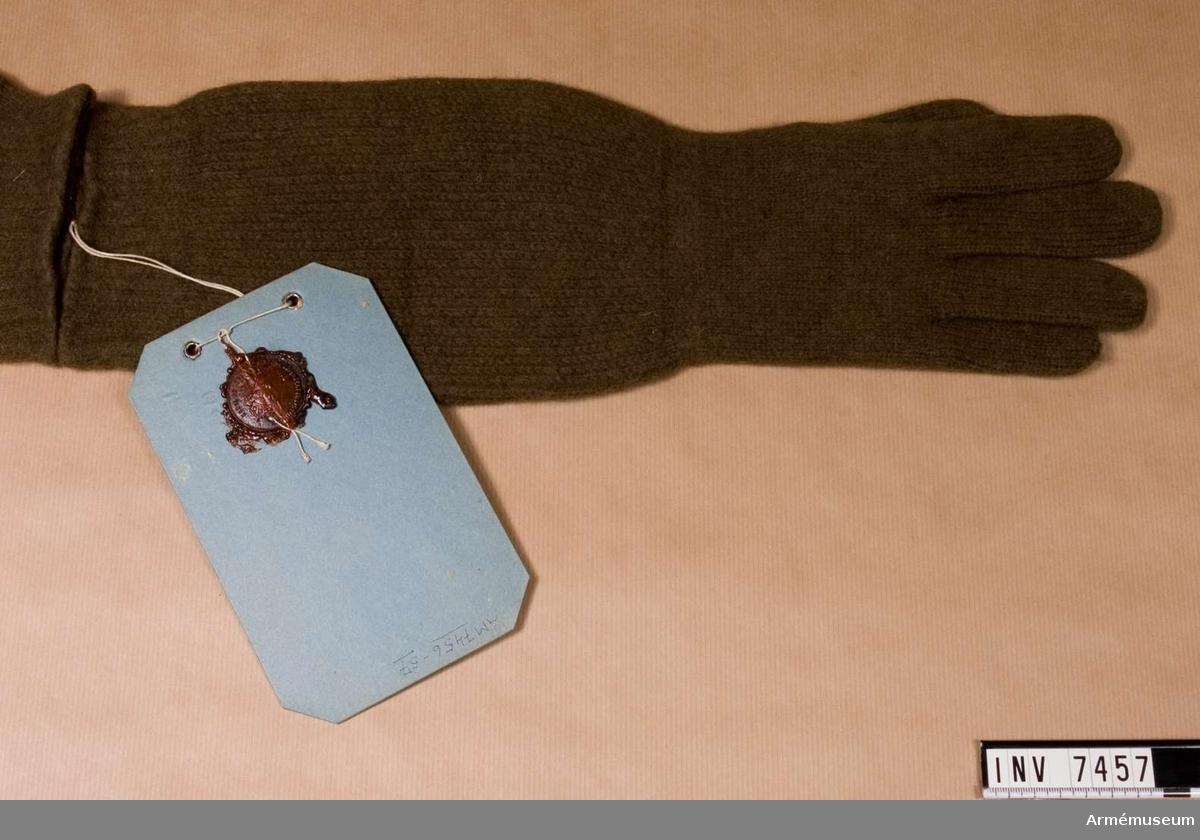 Färg mörkgrön P. Stickad, något valkad vante med tumme och övriga fingrar täckta. Är försedd med långt skaft som går över hela underarmen.   Samhörande par är AM.7456-7457