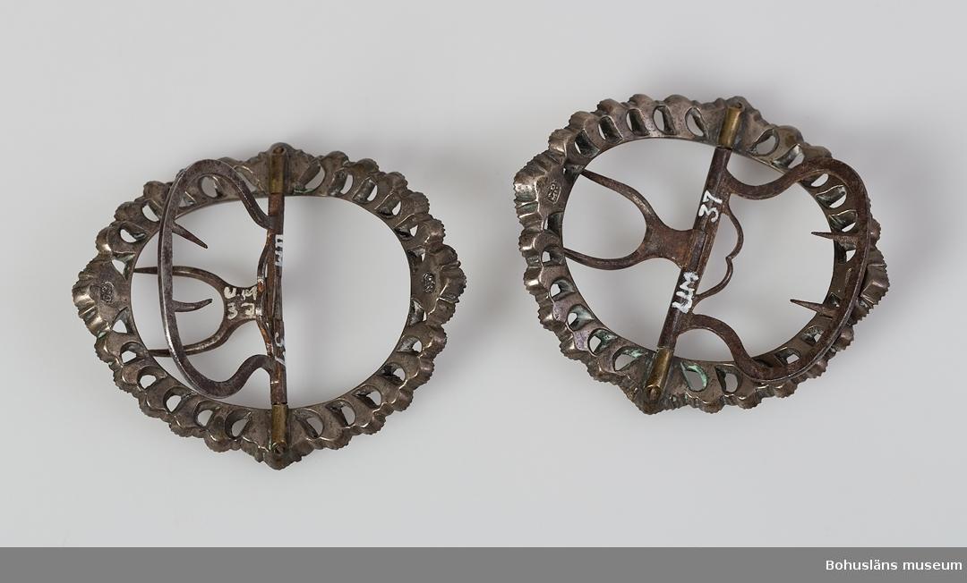 Ett par ovala skospännen, troligen för damskor. Spänntornar av stål,, något rostiga. Spännen med slipade infattade stenar av glas som sitter i par och fyra romber med fyra stenar i varje. Vitmetall, kanske silver i spännena, som är stämplade DR på två ställen på undersidan.  Något rostiga järn-/ståldelar. Rokoko. G:28 i 1869 års tryckta katalog.  Ur handskrivna katalogen 1957-1958: Skospännen av stål Mått c:a 6 x 5,5 cm. Stål m. slipade stenar (briljanterade). Något rostiga. Hela.  Lappkatalog: 78