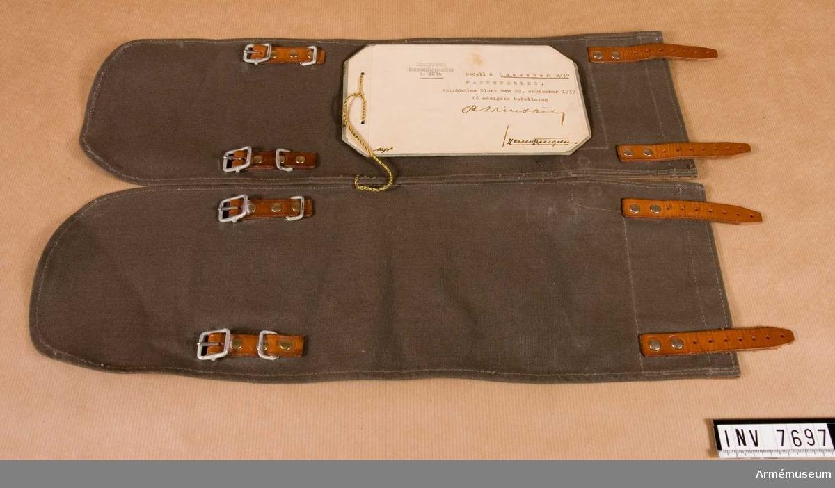 Grå damasker med läderskoning och lås i mellanfärgat brunt läder och med förkromade spänne och nitar. Gott skick 211. Fastställes Stockholms slott den 22 september 1939 nr 2236. På nådigste befallning. Lantförsvarets kommandoexpedition nr 2236.
