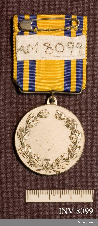 Samhörande AM 8076-. Diameter 35 mm. Tjocklek 1 mm. Bandets höjd 35 mm. Bandets bredd 35 mm. På åtsidan (adversen) Värmlands vapen, landstormsmärken två stycken samt text i kanten: Värmlands Landstormsförbund. Frånsidan (reversen) är ograverad, har en lagerbladskrans och bär stämplarna S 8 Co 0 8. Medaljen hänger i ett gult ripsband med fyra smala blå ränder. Förvaras i blå ask med sammetsbotten märkt C C Sporrong & CO.