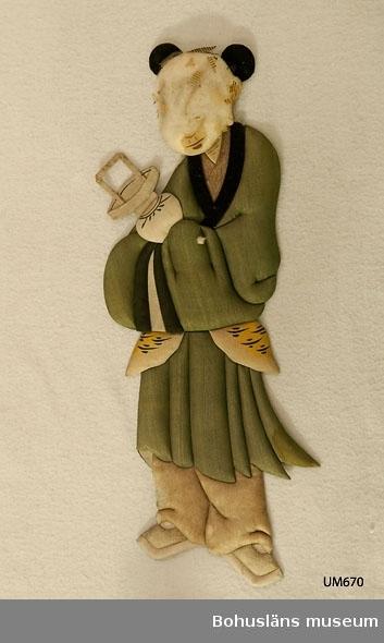 Ur handskrivna katalogen 1957-1958: Kinesiska målad på rispapper,Kina H. 34 cm; en docka gjord på samma sätt som föreg. (UM000669). Ngt trasig, ansiktet förstört.  Lappkatalog: 10  Ur handskriven katalog över Uddevalla Museihistoriska - samlingars Utländska föremål = etnografiska avdelning upprättad  år 1916 av Knut Adrian Andersson, Intendent från 1 Oktober 1915: Kinesisk hustru, målad på tunnt s.k. rispapper och överklädd av bomulls-stomme. Kinesiskt arbete. Sk. 1861 av änkefru Jonssén.