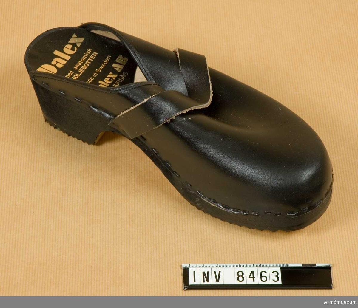FMV:Bekläd skr 183-06-01 Int A 617:331/83. Av svart läder med anatomisk träbotten. Storlek 41. Kronmärkt i hålforten och märkt i hälen: Dalex med anatomisk HOLJEBOTTEN. Made in Sweden Dalex AB BJURSÅS. Holje är namnet på den räfflade gummisulan.