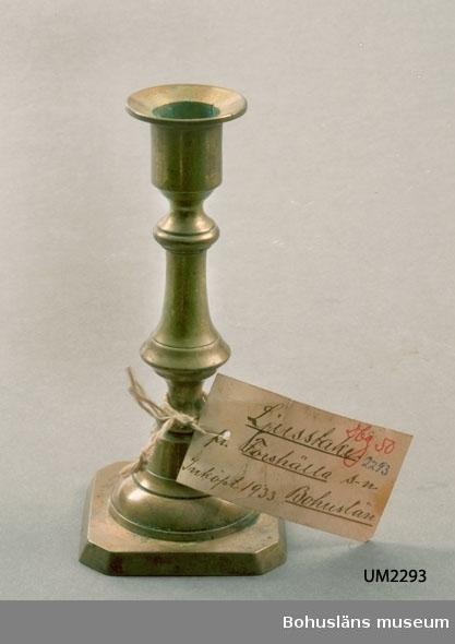 Ur handskrivna katalogen 1957-1958: Ljusstake av mässing Bottenmått: 7 x 7 H: 15. Föremålet helt. Forshälla, Bohuslän.  Lappkatalog: 90