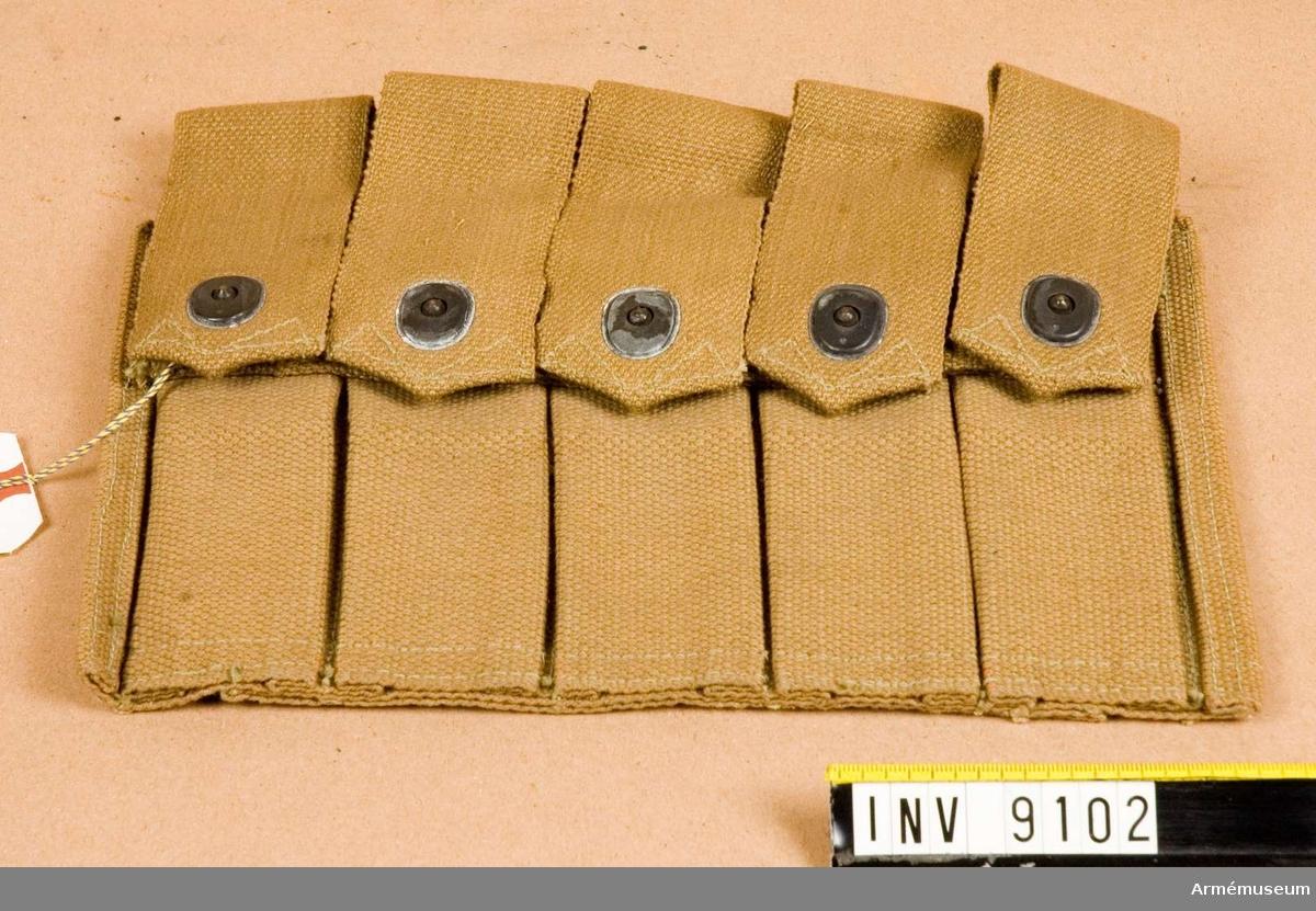 Magasinsväska till kulsprutepistol m/1940, Thompson. För fem stycken 20-skotts stångmagasin till kulsprutepistol m/1940, Thompson. Fem stycken stångmagasinfickor med tryckknappslåsning. Tillverkat i ljusbrunaktig väv.